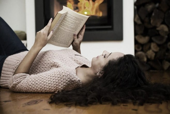 Lady lying on the floor and reading a book on branding, by the fireplace.