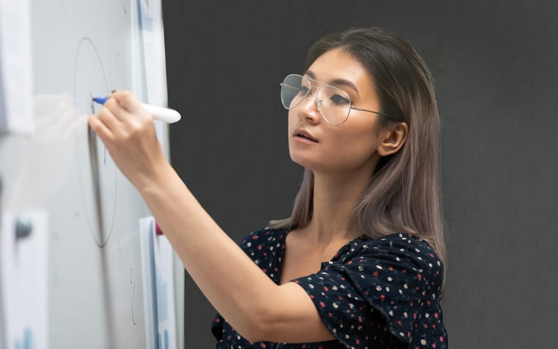 A young Singaporean woman writing on a whiteboard at an information design course in Singapore.