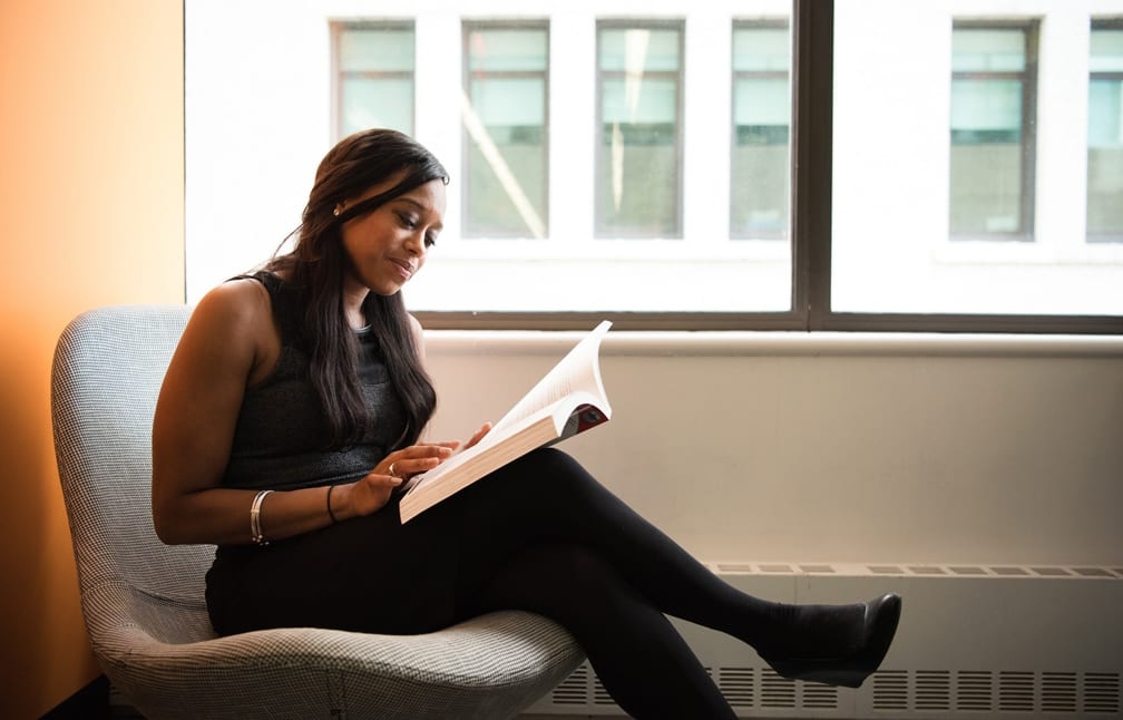 Young African woman reading a book near an office window at a copywriting course in Singapore.